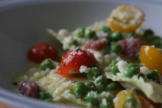 Ravioli with peas, salami & tomatoes